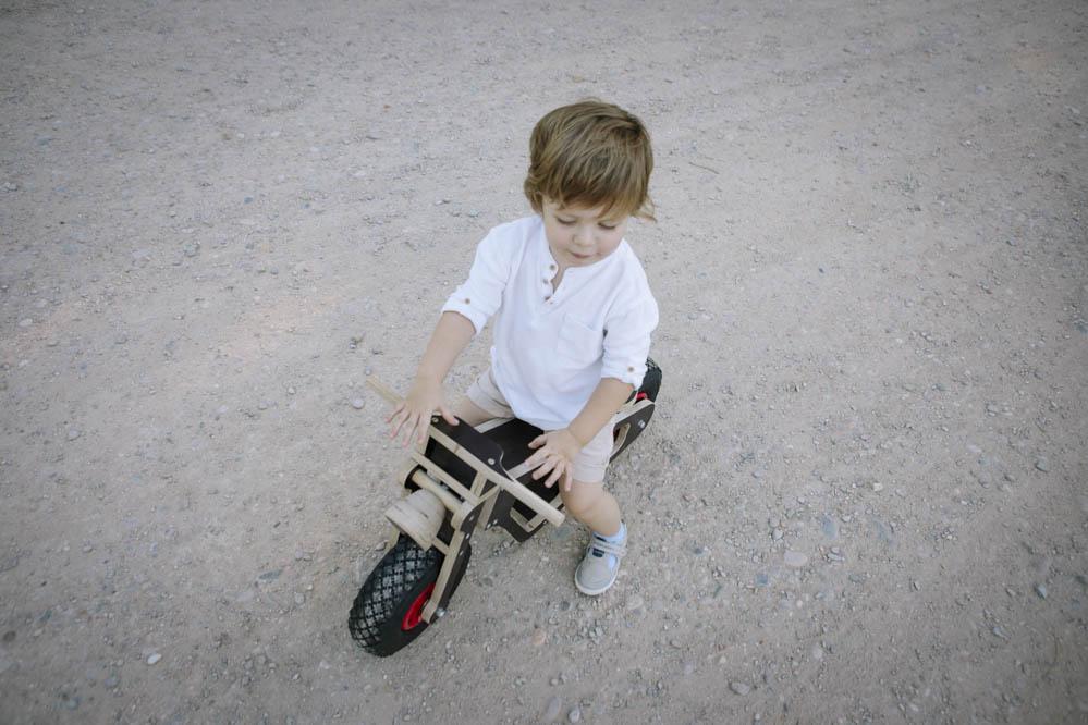niño con bici de madera