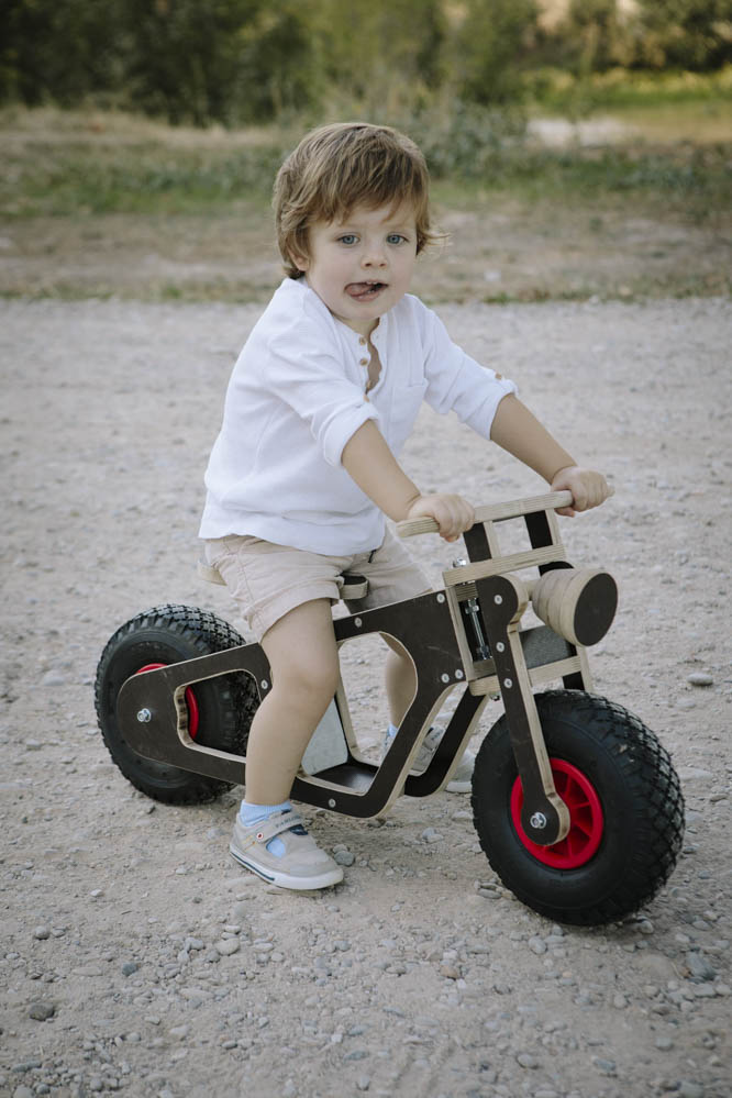 niño con bici de madera 3