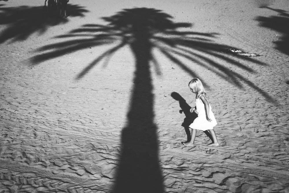 Foto en blanco y negro de niña con palmera